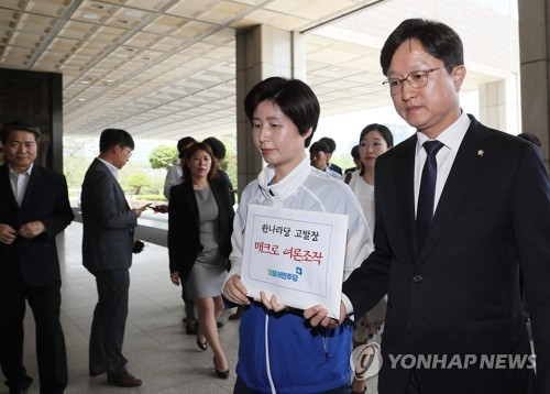 Two spokespersons of the ruling Democratic Party walk into the Seoul Central District Prosecutors' Office to submit a complaint against the main opposition Liberty Korea Party over alleged online opinion rigging on June 7, 2018. (Yonhap)