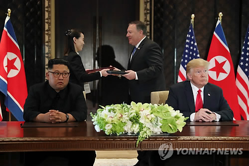 This photo shows U.S. President Donald Trump (R) and North Korean leader Kim Jong-un (L) at the Capella Hotel in Singapore after signing a landmark agreement aimed at denuclearization of the Korean Peninsula on June 12, 2018. (Yonhap)