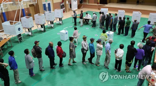 Voters stand in line at a polling station in Chuncheon Gangwon Province to cast their ballots in South Korea's local government elections