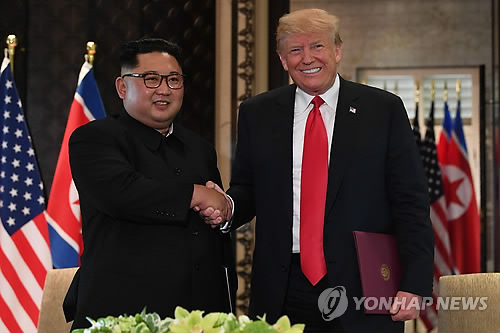 This AFP photo shows U.S. President Donald Trump (R) shaking hands with North Korean leader Kim Jong-un after signing a joint statement at the Capella Hotel on Sentosa Island in Singapore on June 12, 2018. (Yonhap)