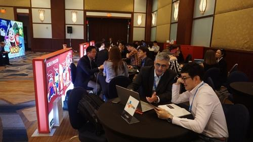 Participants talk at the Korean booth at Kidscreen Summit held in Miami from Feb. 12-15, 2018. (Yonhap)