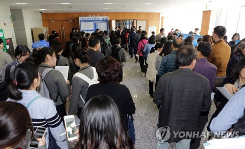 Jobseekers wait in line at a job fair organized by a district office in Seoul on March 29, 2018. (Yonhap)