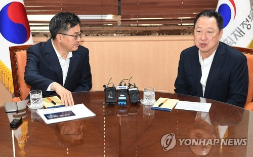 Finance Minister Kim Dong-yeon (L) holds a meeting with Park Yong-maan, chairman of the Korea Chamber of Commerce and Industry (KCCI), in Seoul on June 15, 2018. (Yonhap)