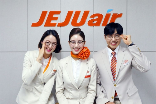 This promotional image provided by Jeju Air shows its flight attendants wearing glasses. (Yonhap)