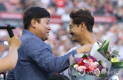 Park Yong-taik of the LG Twins (R) is congratulated by former star Yang Joon-hyuk after breaking Yang's Korea Baseball Organization record with his 2,319th hit against the Lotte Giants in the bottom of the fourth inning of their regular season game at Jamsil Stadium in Seoul on June 23, 2018. (Yonhap)