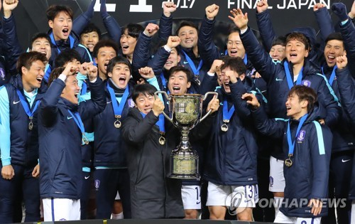 This file photo take on Dec. 16, 2017, shows South Korea national football team head coach Shin Tae-yong (C) lifting a champion's trophy after winning the East Asian Football Federation (EAFF) E-1 Football Championships in Tokyo. (Yonhap)