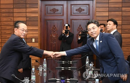 This photo provided by the unification ministry shows Vice Transport Minister Kim Jeong-ryeol (R) shaking hands with his North Korean counterpart Pak Ho-yong before starting talks on inter-Korean cooperation on modernizing and connecting their roads at the truce village of Panmunjom on June 28, 2018. (Yonhap)