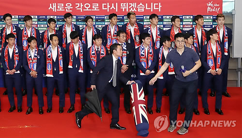 Security officials clear away a pillow thrown toward the South Korean men's national football team at Incheon International Airport after the players' return from the FIFA World Cup in Russia on June 29, 2018. (Yonhap)