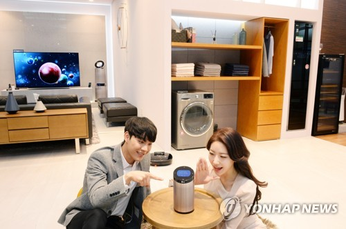 Models pose for a photo with LG Electronics Inc.'s products in this photo released by the company on April 25, 2018. (Yonhap)