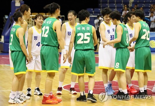 This pool photo taken July 4, 2018, shows South Korean and North Korean women's basketball players shaking hands after their friendly game at Ryugyong Chung Ju-yung Gymnasium in Pyongyang. (Yonhap)