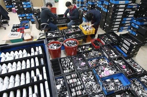 Employees at a used-handset retailer in Uiwang, south of Seoul, inspect devices in this file photo taken June 2, 2016. (Yonhap)