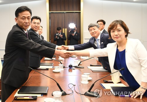 This photo, provided by South Korea's unification ministry on July 4, 2018, shows South and North Korean officials shaking hands before holding working-level talks on forestry cooperation. (Yonhap)