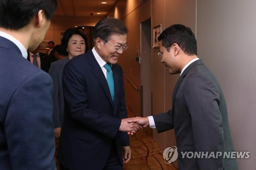 South Korean President Moon Jae-in (second from R) shakes hands with a Singaporean official after arriving in Singapore on July 11, 2018, for a three-day state visit. (Yonhap)
