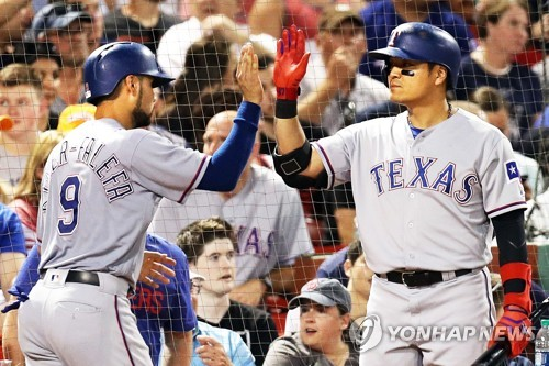 This Getty Images photo shows Texas Rangers' Choo Shin-soo (R) high-fiving Isiah Kiner-Falefa during a Major League Baseball game between the Texas Rangers and the Boston Red Sox at Fenway Park in Boston on July 10, 2018. (Yonhap)