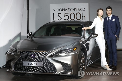 In this photo taken on Dec. 20, 2017, models stand beside the Lexus LS 500h model in Seoul. (Yonhap)