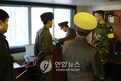 This photo taken in 2007 shows North Korean and United Nations Command officials checking the Panmunjom phone line. (Yonhap)