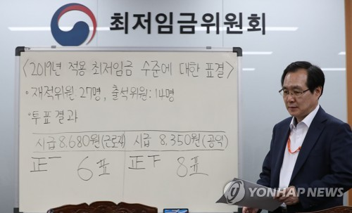 Ryu Jang-soo, the chairman of Minimum Wage Commission under the labor ministry, enters a press conference room to announce the voting result for the 2019 minimum wage at the government complex in Sejong, south of Seoul, on July 14, 2018. (Yonhap)