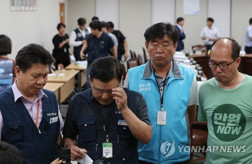 The Minimum Wage Council members representing labor circles react after the voting result for the 2019 minimum wage turned out against what they favored at the government complex in Sejong, south of Seoul, on July 14, 2018. (Yonhap)