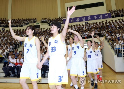 This pool photo taken July 4, 2018, shows women's basketball players from South Korea and North Korea entering the court at Ryugyong Chung Ju-yung Gymnasium in Pyongyang for a friendly basketball match. (Yonhap)