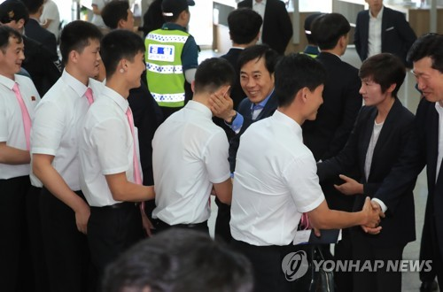 South Korean table tennis legends Hyun Jung-hwa (2nd from R) and Yoo Nam-kyu shake hands with departing North Korean players at Incheon International Airport, west of Seoul, on July 23, 2018. (Yonhap)
