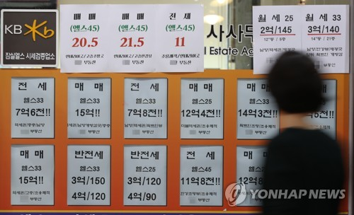 In this file photo taken on July 1, 2018, a passerby walks in front of a realtor's office displaying signs for home leases and home sales. A sign shows the sale price of a 148-square-meter apartment near in Gangnam district is 2.05 billion won (US$1.8 million). (Yonhap)