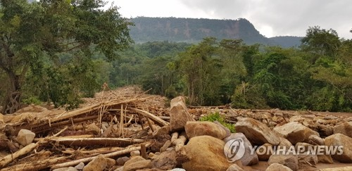 A road to a Laotian village, hit by flash floods caused by a dam failure, is covered with fallen rocks. (Yonhap)