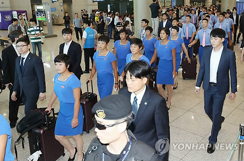 Members of the North Korean delegation for the Asian Games (in blue outfits) arrive at Incheon International Airport, west of Seoul, on July 29, 2018, to begin joint training with South Korean athletes. The Koreas will field unified teams in women's basketball, dragon boat racing in canoeing and three events in rowing at the Aug. 18-Sept. 2 Asian Games in Indonesia. (Yonhap)