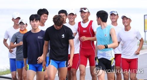 South Korean and North Korean rowers jog together before their practice at Chungju Tangeum Lake International Rowing Center in Chungju, 150 kilometers south of Seoul, on July 30, 2018. These athletes will compete together at the Asian Games in Jakarta and Palembang, Indonesia. (Yonhap)