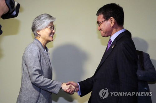 South Korea's Foreign Minister Kang Kyung-wha shakes hands with her Japanese counterpart Taro Kono in Singapore talks on Aug. 2 2018