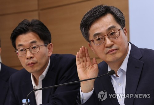 Finance Minister Kim Dong-yeon (R) listens to questions raised after the government outlined its 2018 tax plan on July 30, 2018, in this file photo. (Yonhap)