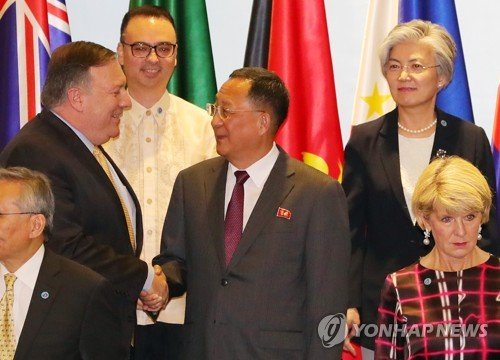 U.S. Secretary of State Mike Pompeo (L) shakes hands with North Korean Foreign Minister Ri Yong-ho at a photo session of the ASEAN Regional Forum in Singapore on Aug. 4, 2018. (Yonhap)
