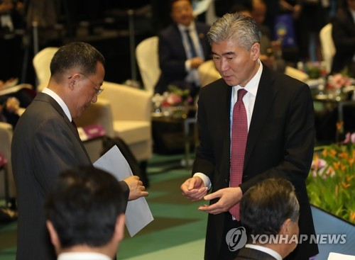 North Korean Foreign Minister Ri Yong-ho (L) receives an envelope of documents from Sung Kim, the State Department's top Korea expert, in Singapore on Aug. 4, 2018. (Yonhap)