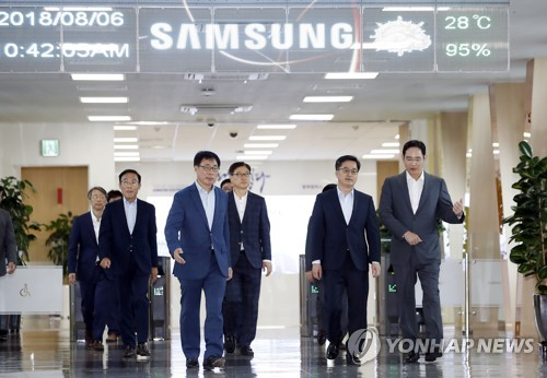 Finance Minister Kim Dong-yeon (2nd from R) talks with Samsung Electronics Vice Chairman Lee Jae-yong (R) while moving into a room for talks at the tech giant's chipmaking line in Pyeongtaek, south of Seoul, on Aug. 6, 2018. (Yonhap)