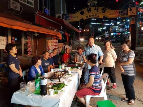 This photo captured from Seoul Mayor Park Won-soon's Facebook page shows Park having a barbecue party with merchants in a traditional market in Samyang-dong, northern Seoul. (Yonhap)