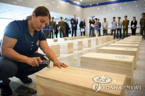 In this image captured from the United States Forces Korea homepage an official from the U.S. Department of Defense drives a nail into one of wood coffins that contain remains of American service members who died during the 1950-53 Korean War in Wonsan