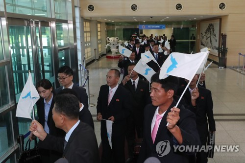 The North Korean delegation for an inter-Korean workers' football match wave unified Korean flags as they arrive in Paju, just south of the border in the South, on Aug. 10, 2018, for a three-day visit as part of the first private-level exchange between the two Koreas since the April summit of the two leaders of the states. (Yonhap)