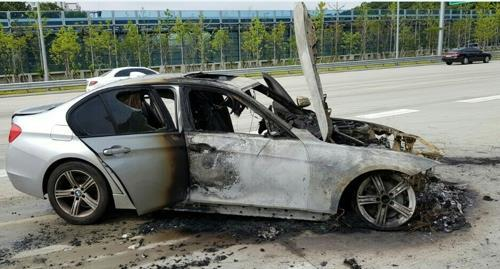 A burned BMW sedan on the side of a road in South Korea (Yonhap)