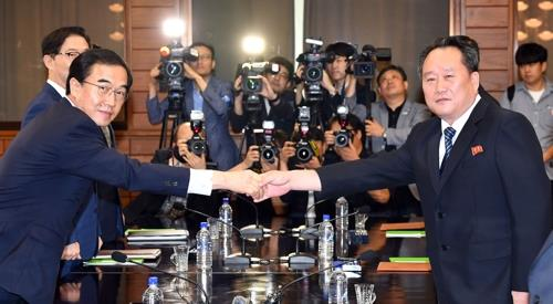This photo taken by joint press corps shows South Korea's Unification Minister Cho Myoung-gyon (L) shake hands with his North Korean counterpart Ri Son-gwon before launching high-level talks on Aug. 13, 2018 on the northern side of Panmunjom to discuss inter-Korean relations and preparations for a summit meeting between their leaders. (Yonhap)