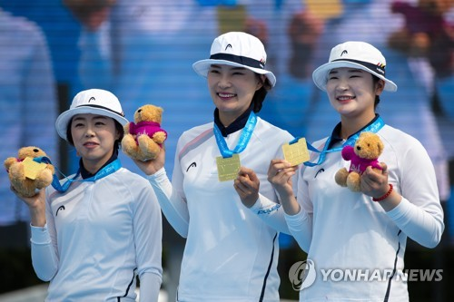 In this EPA file photo from July 22, 2018, South Korean archers Chang Hye-jin, Jung Dasomi and Kang Chae-young (from L to R) hold up their gold medals after winning the women's recurve team title over Britain at the Archery World Cup in Berlin. (Yonhap)