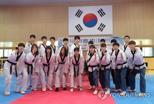 South Korean taekwondo practitioners pose for photos during a media day event at the Jincheon National Training Center in Jincheon, 90 kilometers south of Seoul, on Aug. 8, 2018. (Yonhap)