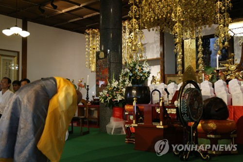 A Buddhist monk bows in front of boxes containing remains belonging to Korean people taken to Japan to work for its factories and military during World War II at Kokuhei Temple in western Tokyo on Aug. 12, 2018. (Yonhap)