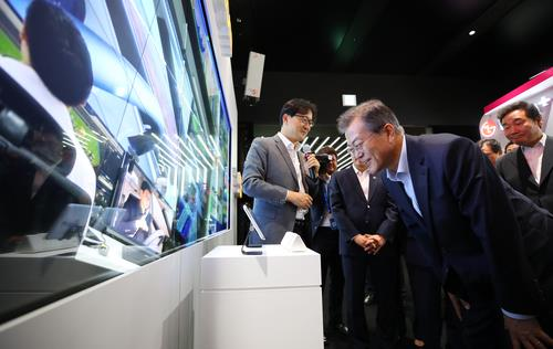 President Moon Jae-in tests a smart media wall using fifth-generation (5G) technology at a research and development complex in Seoul on May 17, 2018. (Yonhap)