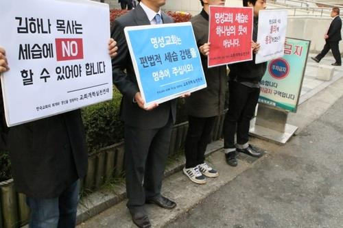 A group of activists picket in denunciation of Myungsung Church's father-to-son succession of the senior pastorship in this photo courtesy of the activists. (Yonhap)