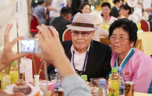 This photo taken by Joint Press Corps shows Yoo Kwan-sik (L), 89, pose for pictures with his long-separated daughter from the North during a group reunion at Mount Kumgang on Aug. 21, 2018. (Yonhap)