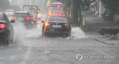 Vehicles move on a submerged road in Jeju City on Aug. 23, 2018, as Typhoon Soulik hit the southern resort island with strong winds and heavy rain. (Yonhap)