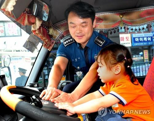 A police officer shows a daycare center child to how to honk the horn if left on a school bus on Aug. 9, 2018, in this photo provided by Seoul Metropolitan Policy Agency. (Yonhap)