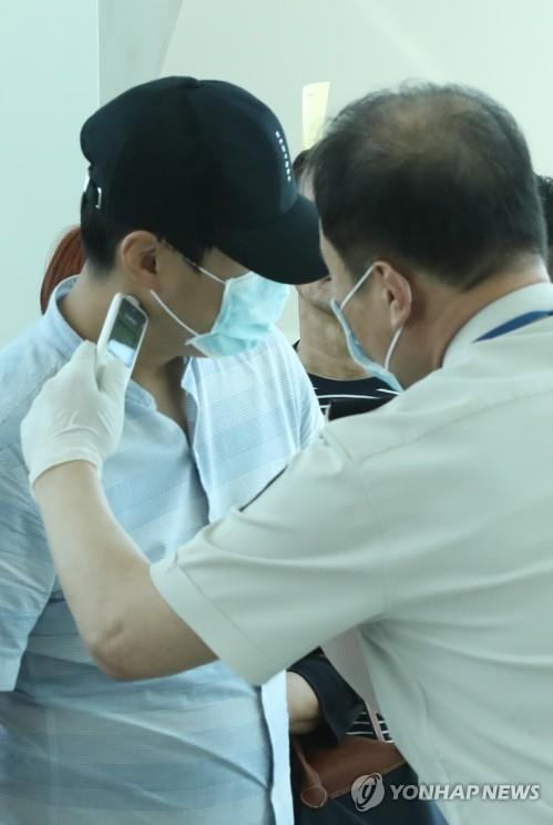 Quarantine officers check the temperatures of passengers arriving at Incheon International Airport, west of Seoul, on flights from Dubai on Sept. 10, 2018, as a preventive measure against the spread of Middle East Respiratory Syndrome (MERS). (Yonhap)