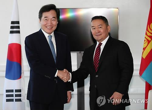 South Korea's Prime Minister Lee Nak-yon (L) shakes hands with Mongolia's President Khaltmaa Battulga before their talks in Russia's far eastern port city of Vladivostok on Sept. 11, 2018. (Yonhap)