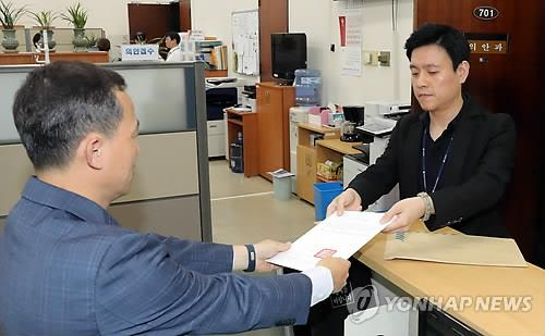 A unification ministry official hands over a motion for the parliamentary ratification of the April inter-Korean summit declaration at the National Assembly in Seoul on Sept. 11, 2018. (Yonhap)