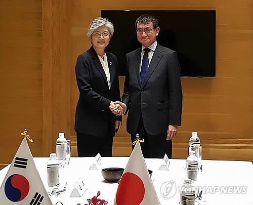 South Korean Foreign Minister Kang Kyung-wha (L) shakes hands with her Japanese counterpart Taro Kono before their talks in Hanoi, Vietnam, on Sept. 11, 2018. (Yonhap)